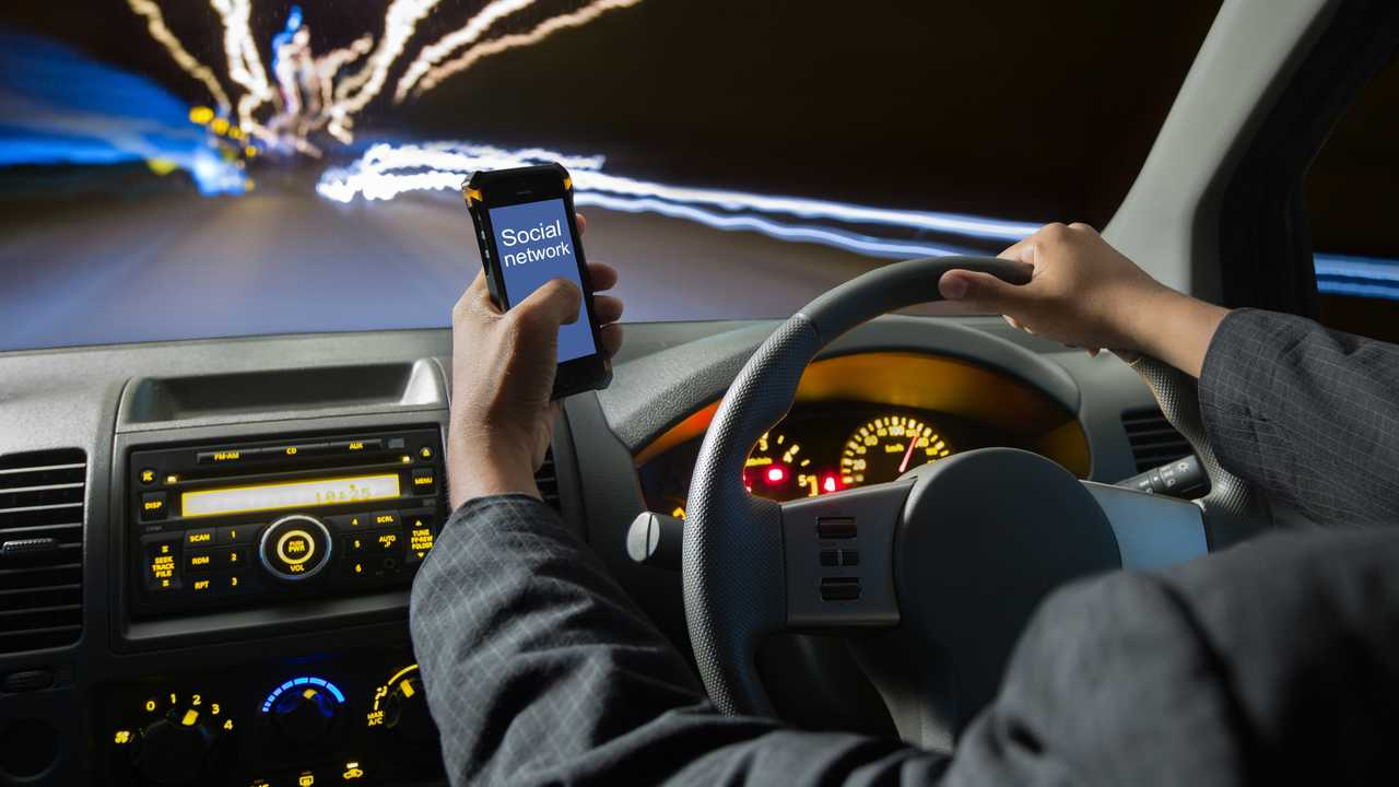 Man using smart phones while driving at night
