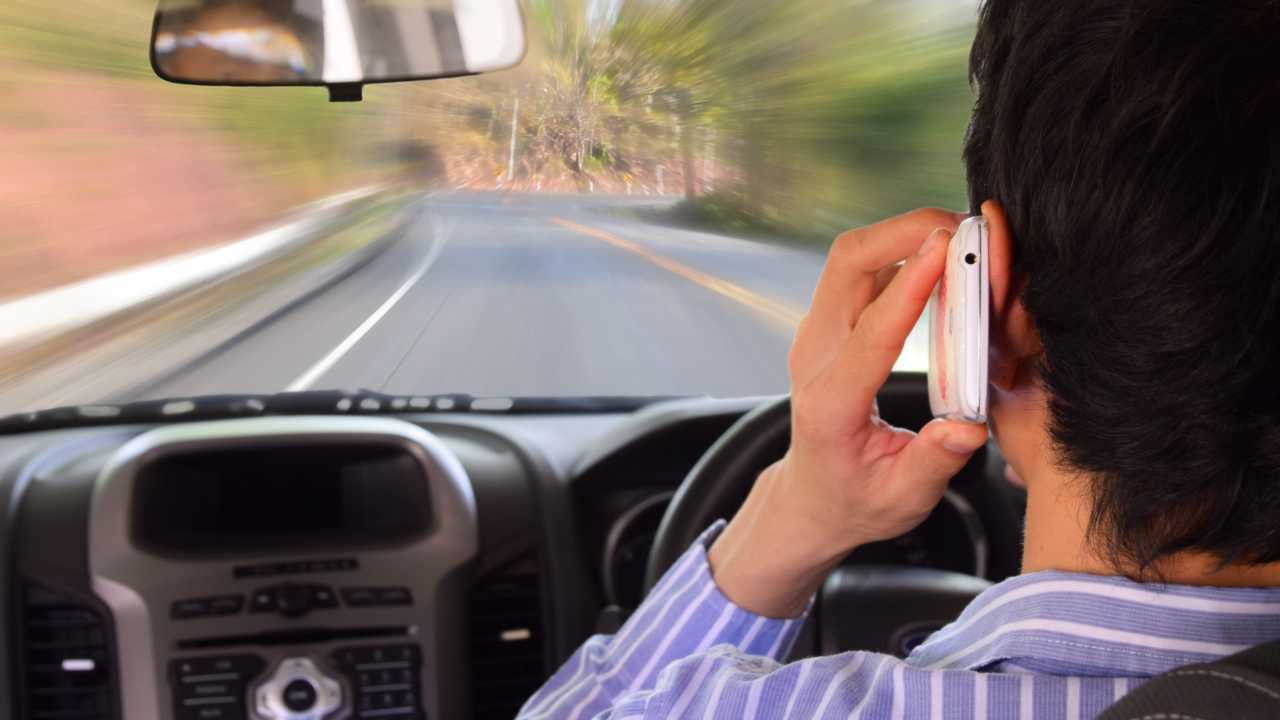 Man driving while talking on a mobile phone