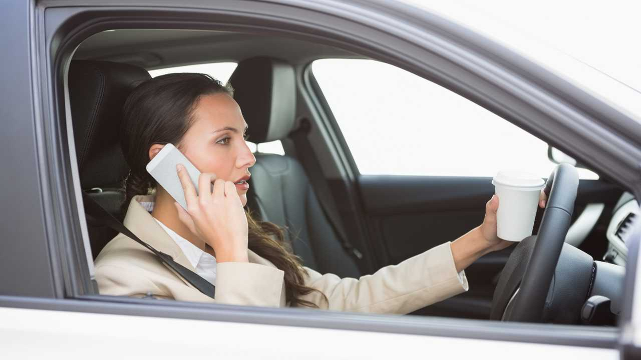 Woman drinking coffee on phone while driving in car