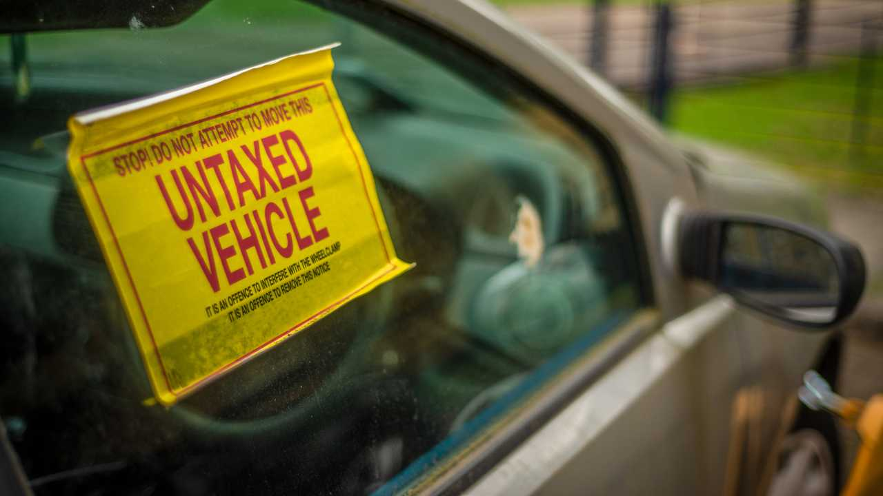 Untaxed vehicle notice on window of car with clamp on front wheel