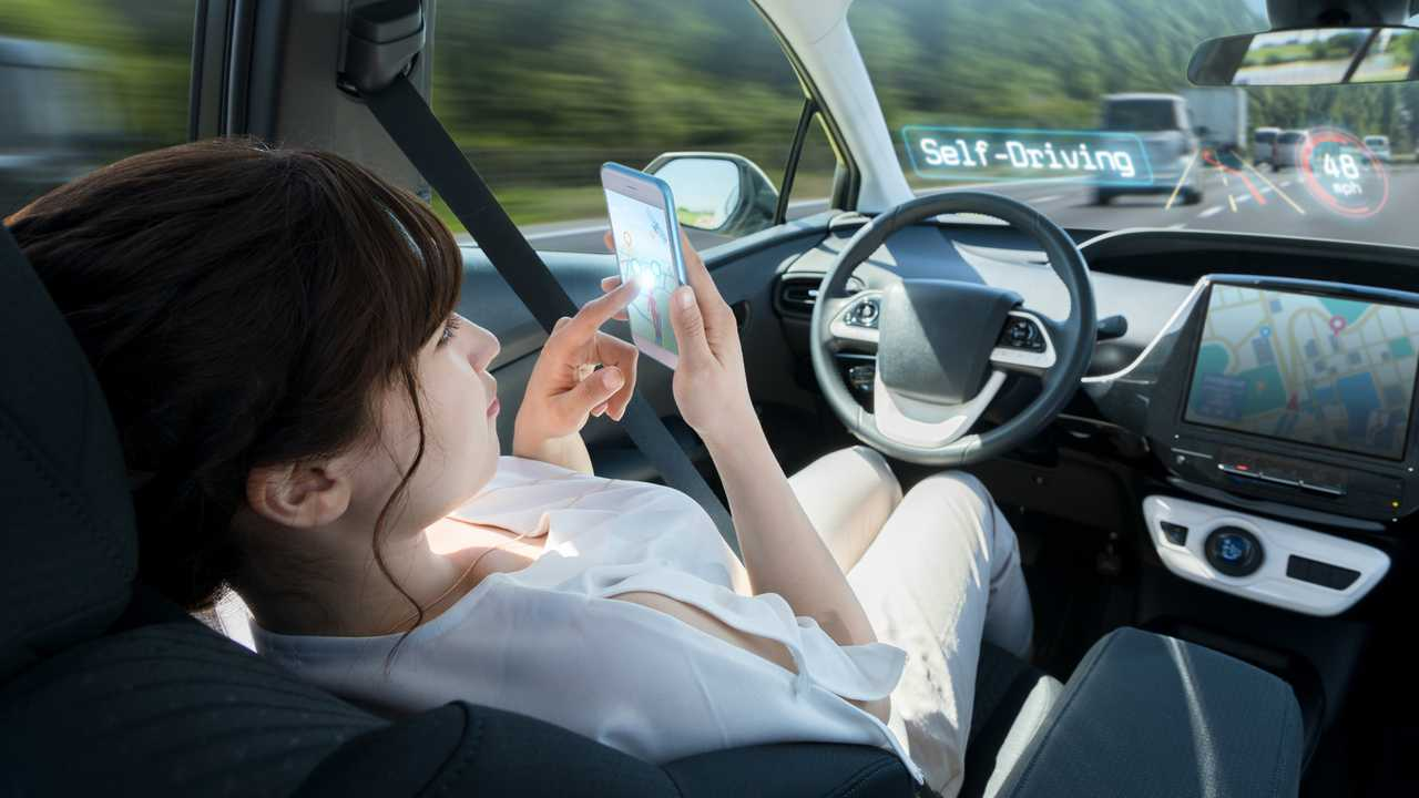 Woman laying back using smart phone in autonomous self driving car