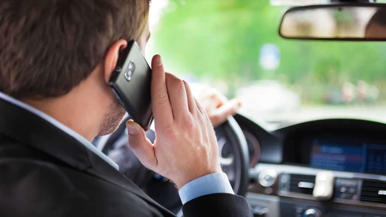 Man talking on the phone while driving his car