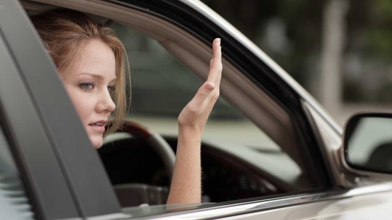 Annoyed young woman driver gesturing with hands