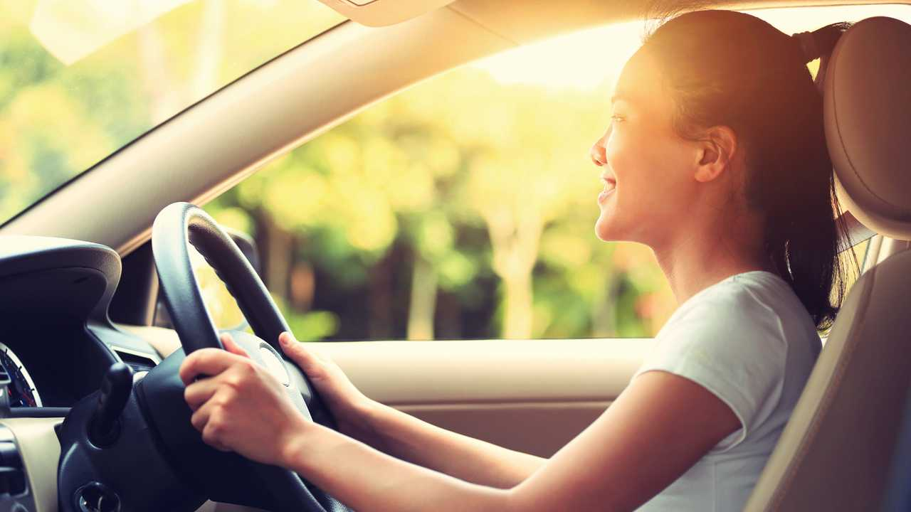 Young woman smiling and driving car