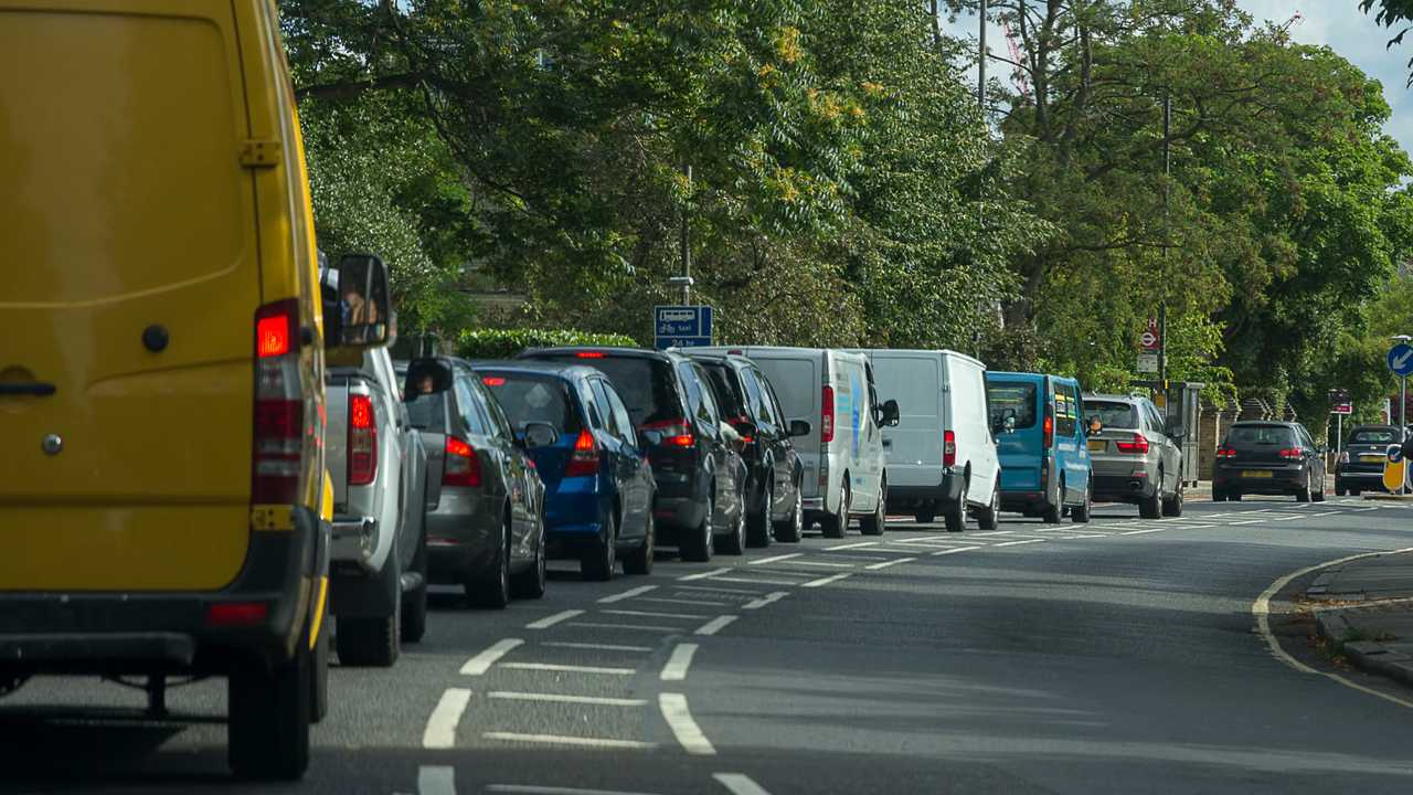 Cars and vans queueing in heavy traffic on a busy London road