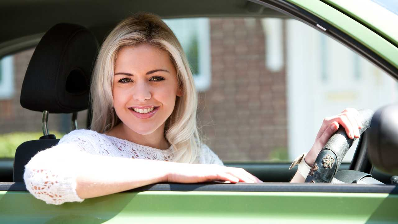 Smiling woman driving with sun shining